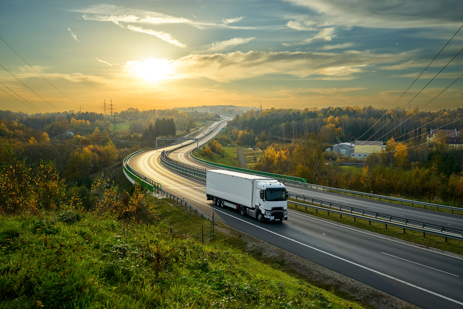 White truck driving on the highway winding through forested landscape in autumn colors at sunset